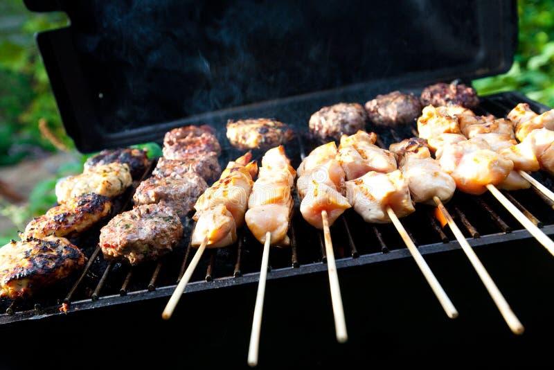 Brutzelnde Burger und Huhn kebabs stockfoto