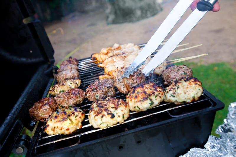Brutzelnde Burger und Huhn kebabs lizenzfreie stockfotografie
