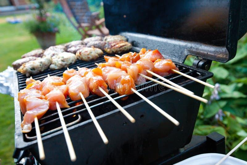 Brutzelnde Burger und Huhn kebabs stockfotografie