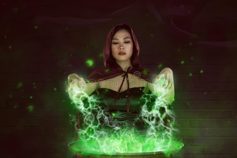 Bruxa asiática da menina com o casaco vermelho que prepara uma poção mágica imagem de stock royalty free