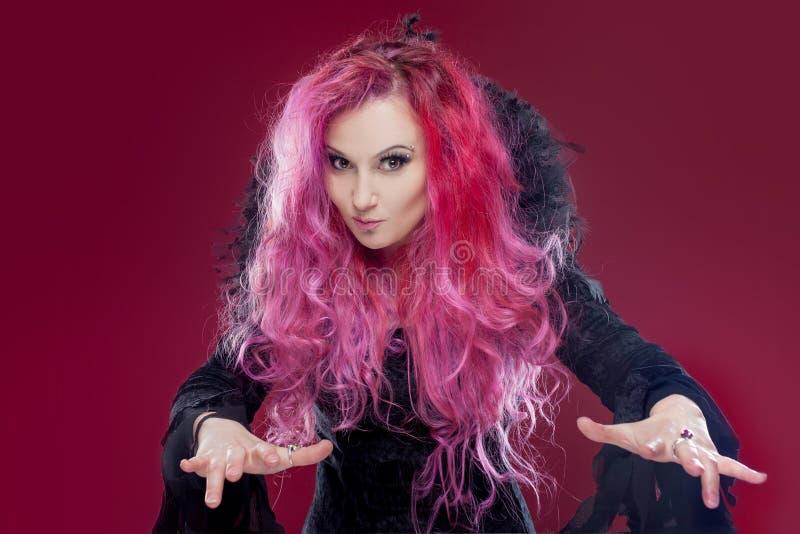 A bruxa assustador com cabelo vermelho executa a mágica em um fundo cor-de-rosa Dia das Bruxas, tema do horror fotos de stock royalty free