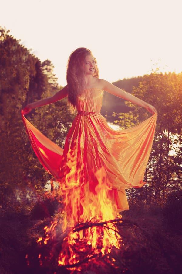 Bruxa bonita nas madeiras perto do fogo Celebrat mágico da mulher foto de stock royalty free