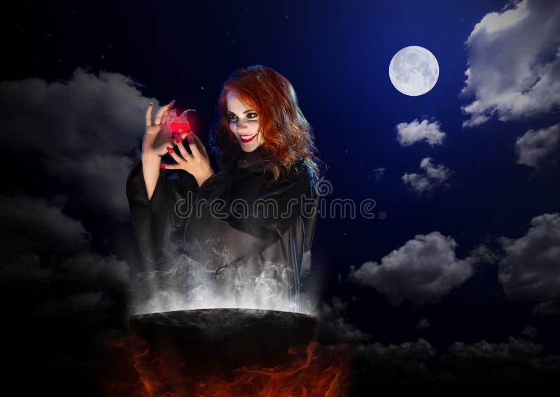 Bruxa com poção vermelha e caldeirão no fundo do céu noturno imagem de stock