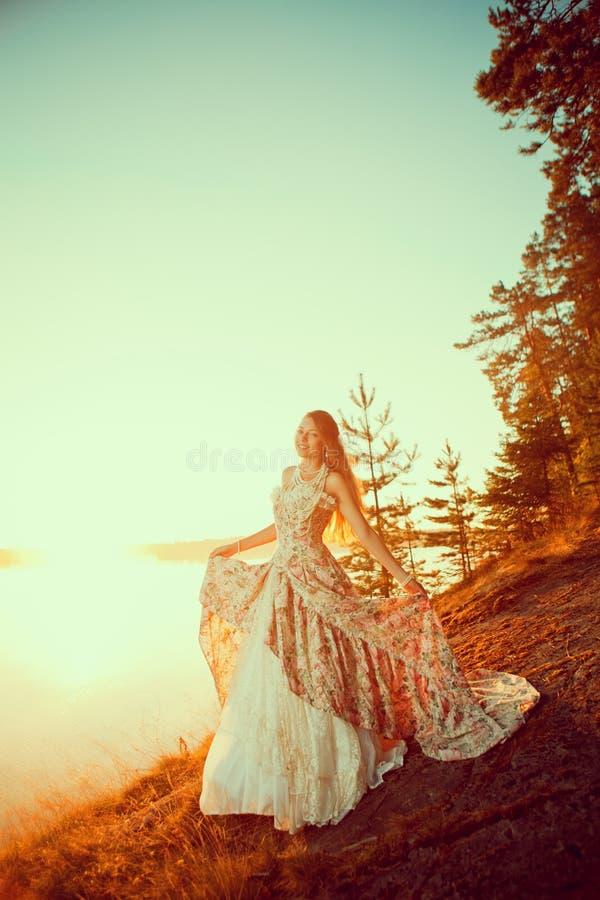 Bruxa da beleza nas madeiras perto do fogo Mulher mágica que comemora fotografia de stock royalty free