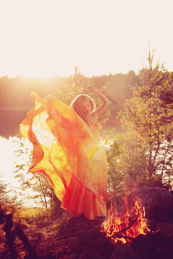Bruxa da beleza nas madeiras perto do fogo Mulher mágica que comemora imagens de stock