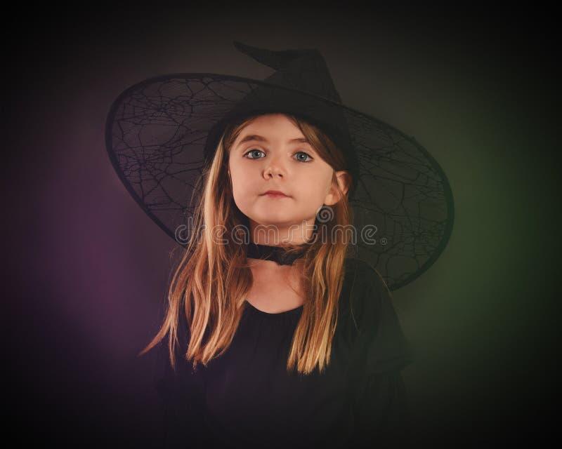 Bruxa da criança de Dia das Bruxas no fundo preto fotografia de stock