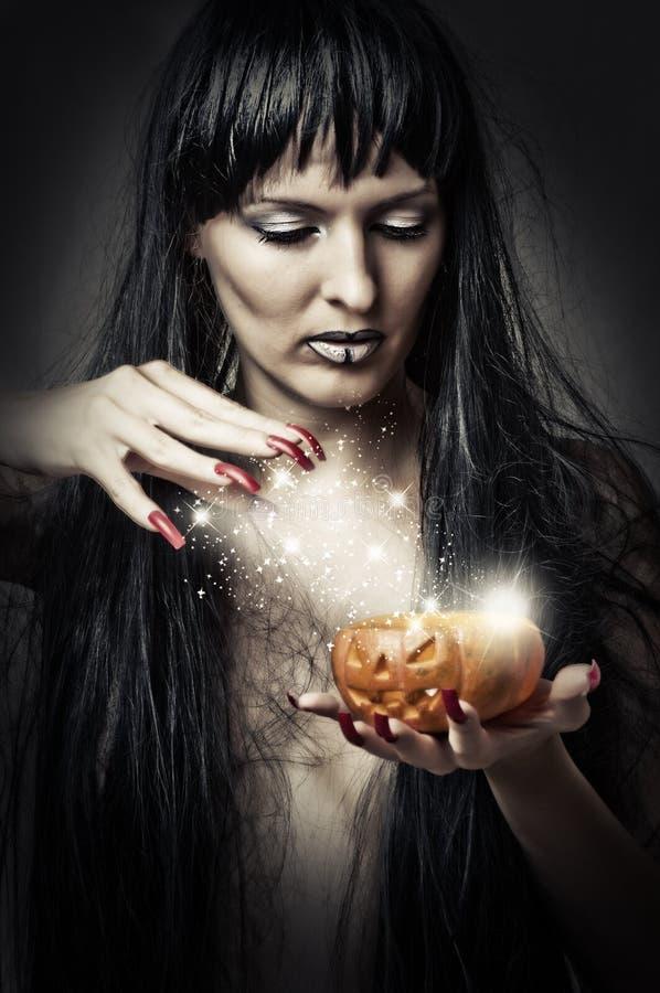 Bruxa da mulher que faz a mágica à abóbora fotos de stock royalty free