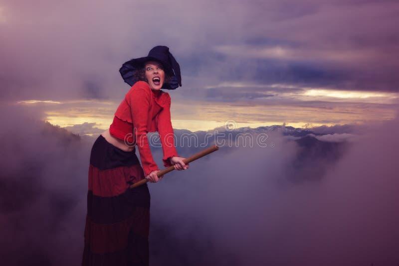 A bruxa de Dia das Bruxas está voando na vassoura imagens de stock royalty free