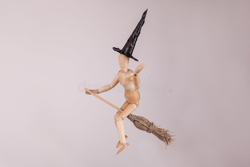 Bruxa de Dia das Bruxas que acena a boneca articulada de madeira do manequim que monta uma vassoura imagens de stock royalty free