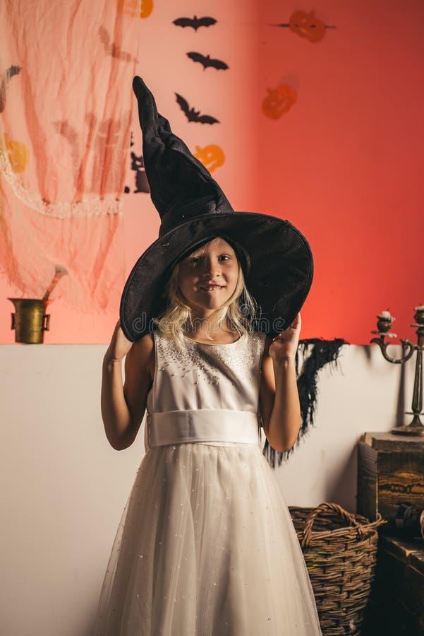 Bruxa de Halloween com ab?bora Criança engraçada em trajes do carnaval dentro Menina da beleza que levanta com decoração de Dia d imagem de stock