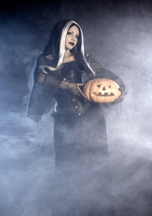 Bruxa de Halloween com uma abóbora. imagens de stock