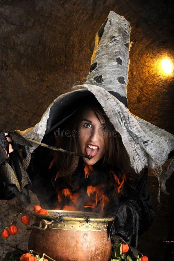 Bruxa de Halloween que cozinha em um caldeirão de cobre fotografia de stock