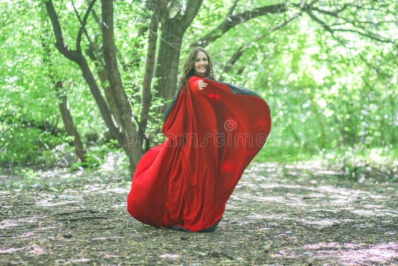 Bruxa em um casaco vermelho entre imagem de stock royalty free