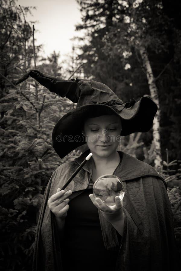 Bruxa escura com varinha e a bola de vidro foto de stock royalty free
