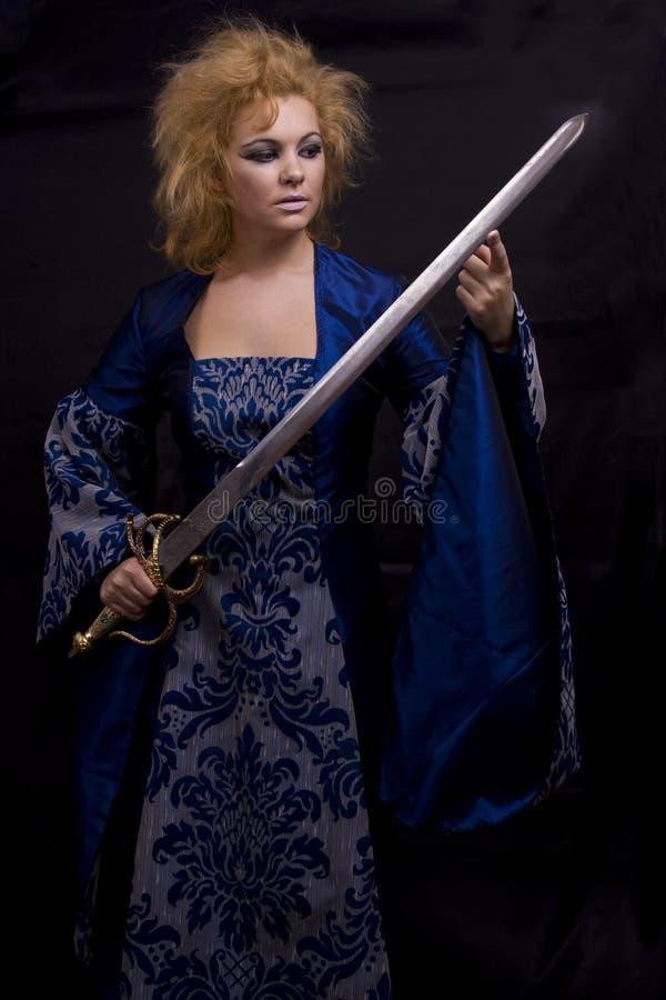 Bruxa horrívea com espada. fotografia de stock