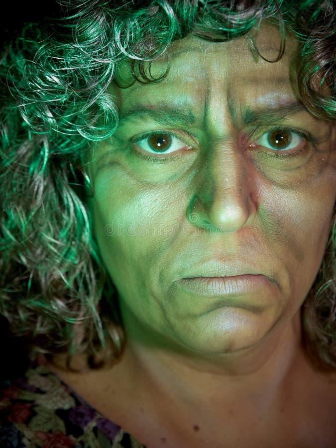 Bruxa idosa na luz verde fotos de stock