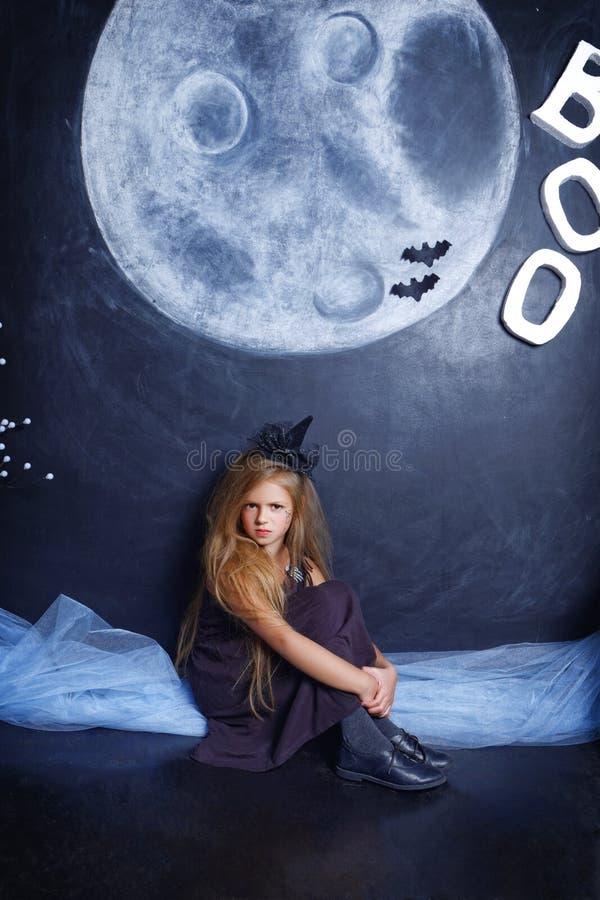 Bruxa má pequena que senta-se no estúdio fotos de stock