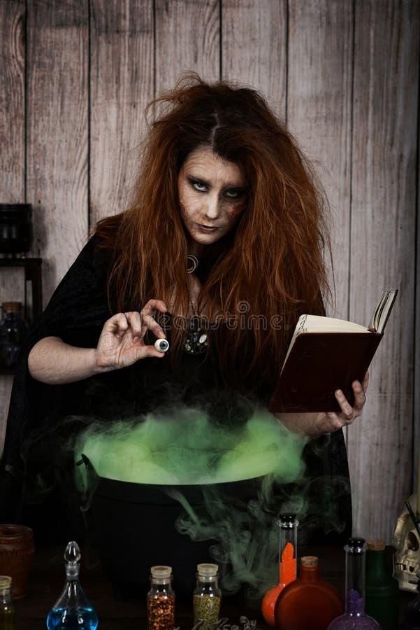 Bruxa má que adiciona um globo ocular a sua poção mágica foto de stock