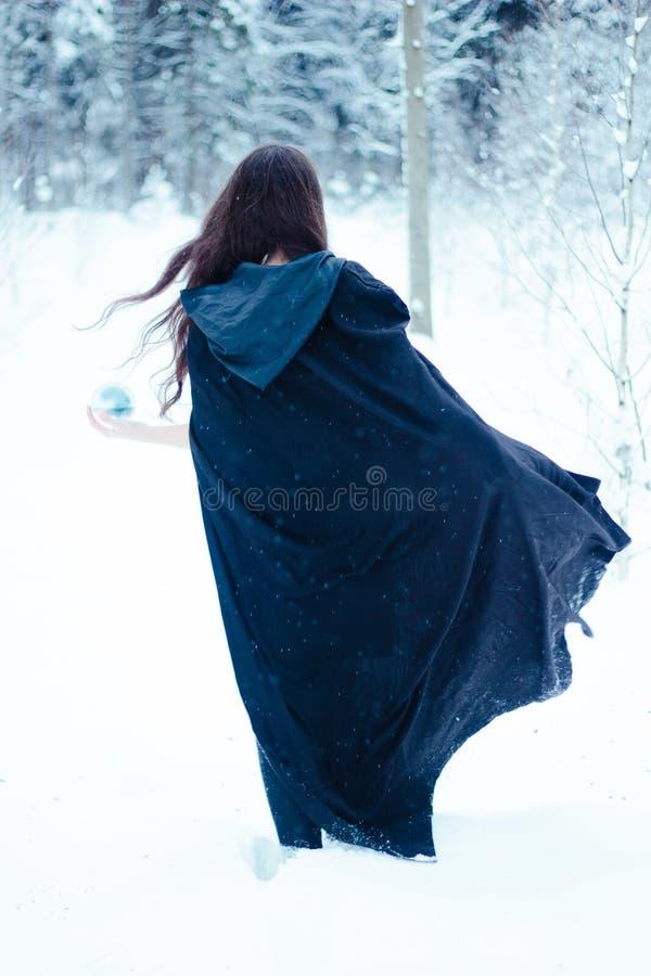 Bruxa no casaco preto com a bola do  do magiÑ imagem de stock