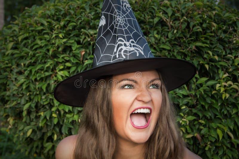 Bruxa nova bonita no chapéu negro que grita foto de stock royalty free