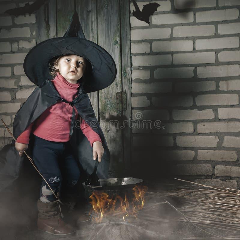 Bruxa pequena que faz uma poção mágica na noite de Dia das Bruxas horror foto de stock