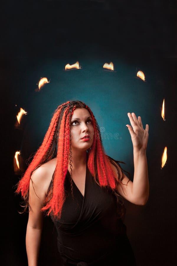 A bruxa pratica a feitiçaria no fundo preto. imagens de stock royalty free