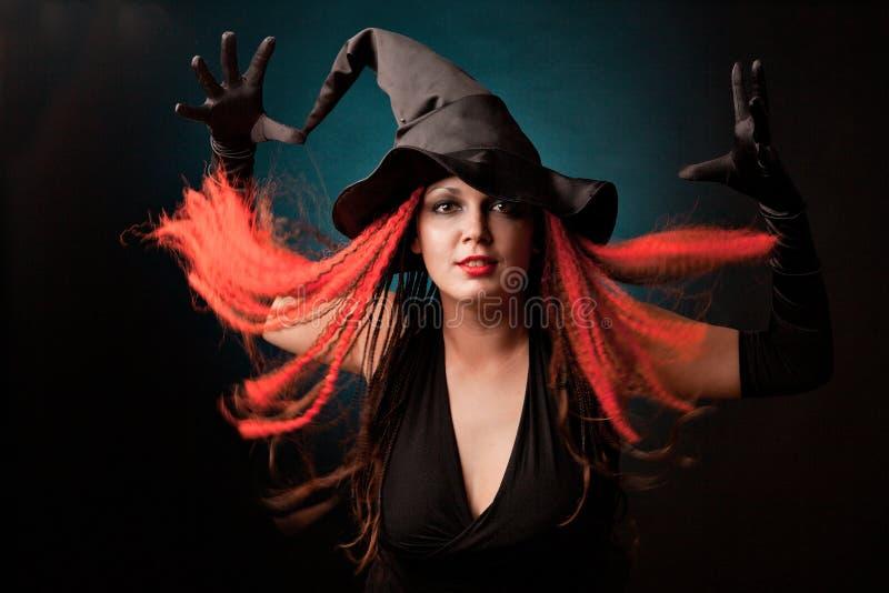 A bruxa pratica a feitiçaria no fundo preto. imagens de stock