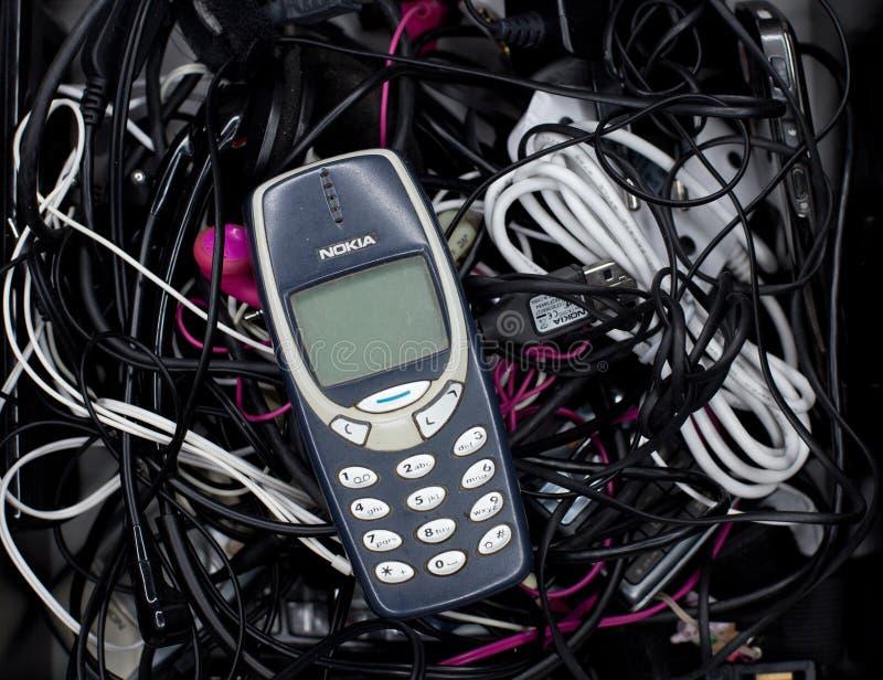 Bruxelas, Bélgica - 26 de fevereiro de 2017: O telefone celular icônico de Nokia 3310 fotografou em uma pilha de cabos de carrega imagem de stock