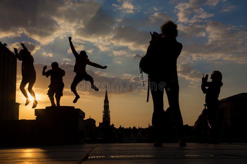Bruxelles - silhouette des garçons sautés au-dessus de la ville sur des arts de DES de Monts dans la soirée photographie stock