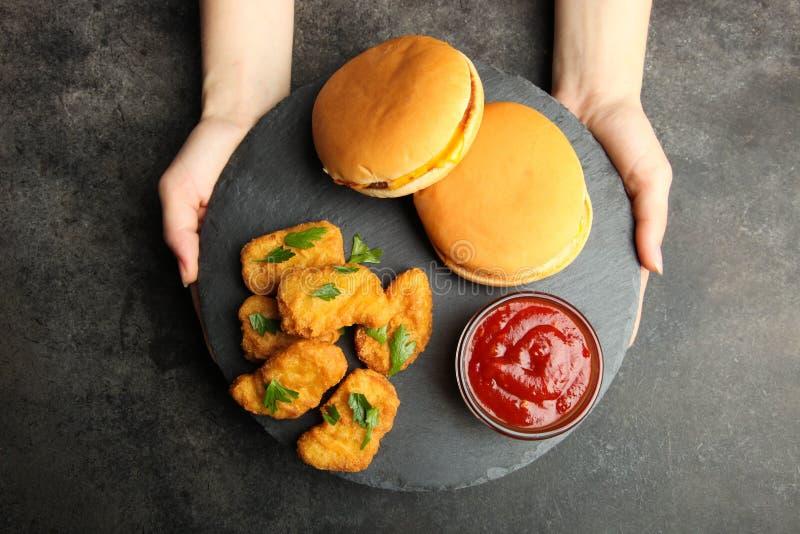 Bryłki, dwa cheeseburgers i chili kumberland na łupku, wsiadają obrazy royalty free