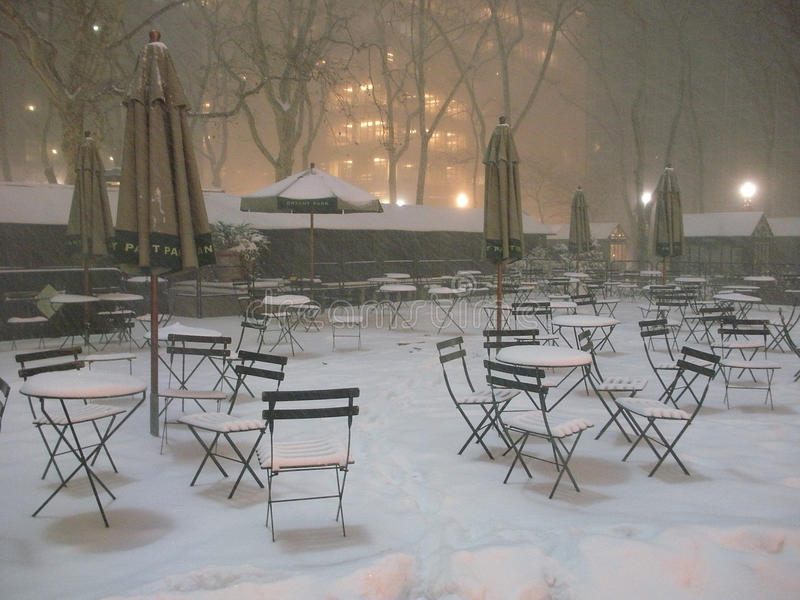 Bryant Park in the Snow, New York City, USA. A wintry scene, snow is falling on the iconic green chairs, cafe tables, and patio umbrellas of Bryant Park stock photos