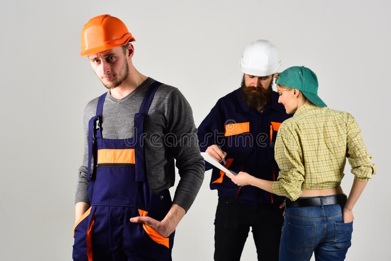 Brygada pracownicy, budowniczowie w hełmach, naprawiacze i dama dyskutuje kontrakt, popielaty tło Rekrutacyjny pojęcie zdjęcia stock