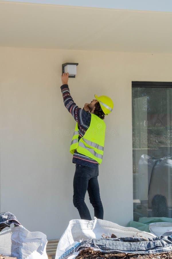 Brygadier sprawdza instalacji zewnętrzny oświetlenie na budynku w budowie, miejsce wizyta zdjęcie royalty free
