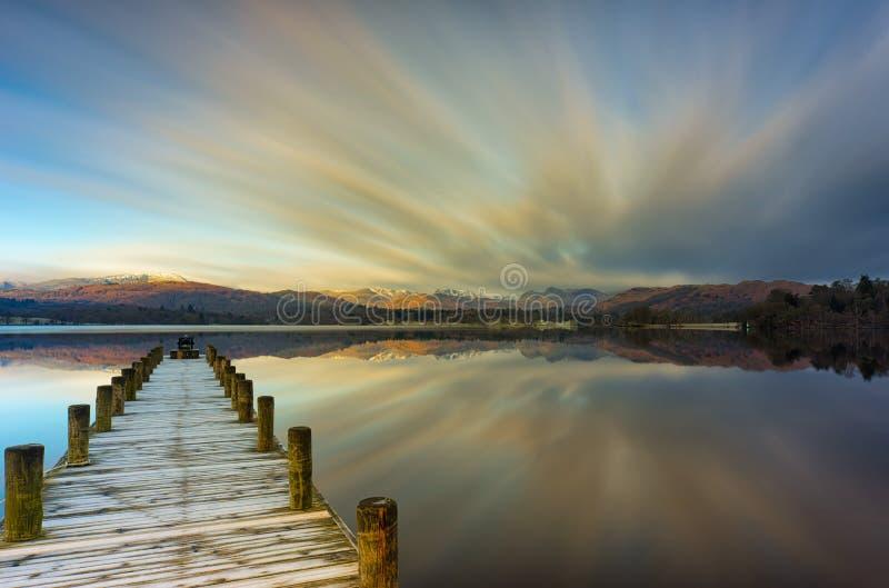 Brygga över Windermere sjön med att göra strimmig moln arkivfoto