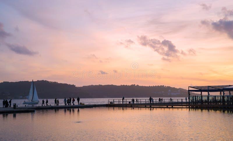 Brygga med folk- och segelbåtkonturn under solnedgång royaltyfri foto