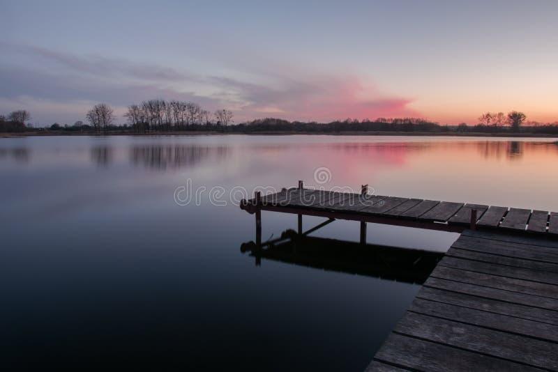Brygga med plankor på en lugna sjö och rosa moln efter solnedgång arkivbild