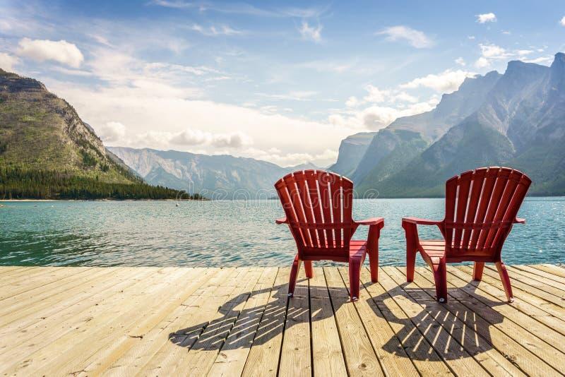 Brygga med stolar vid Minnewanka sjön, Alberta, Kanada royaltyfria foton