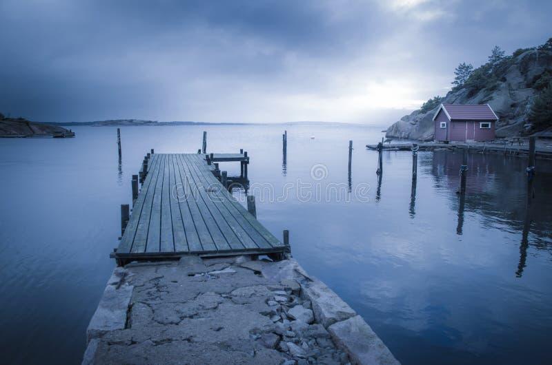 Brygga och sjöbod vid fjorden arkivbilder