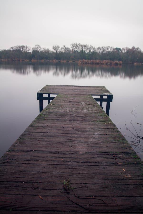 Brygga på Earlswood sjöar på en vintermorgon arkivbild