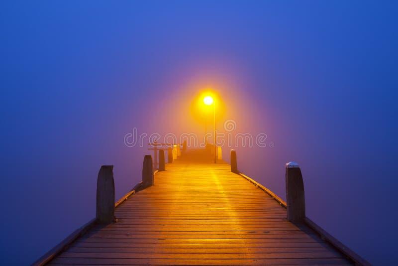 Brygga på en dimmig morgon på gryning arkivbild