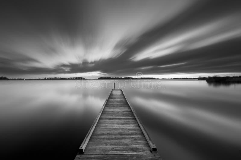 Brygga på en sjö i svartvitt arkivbild