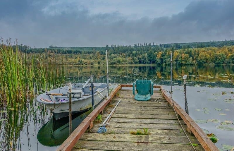 Brygga på en sjö med det lilla fartyget royaltyfri bild
