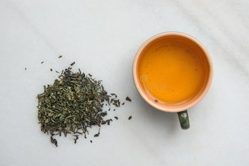 Bryggat grönt te i keramisk kopp Lösa sidor spridda på vit marmorstenbakgrund Kinesisk japansk asiatisk kokkonst fotografering för bildbyråer