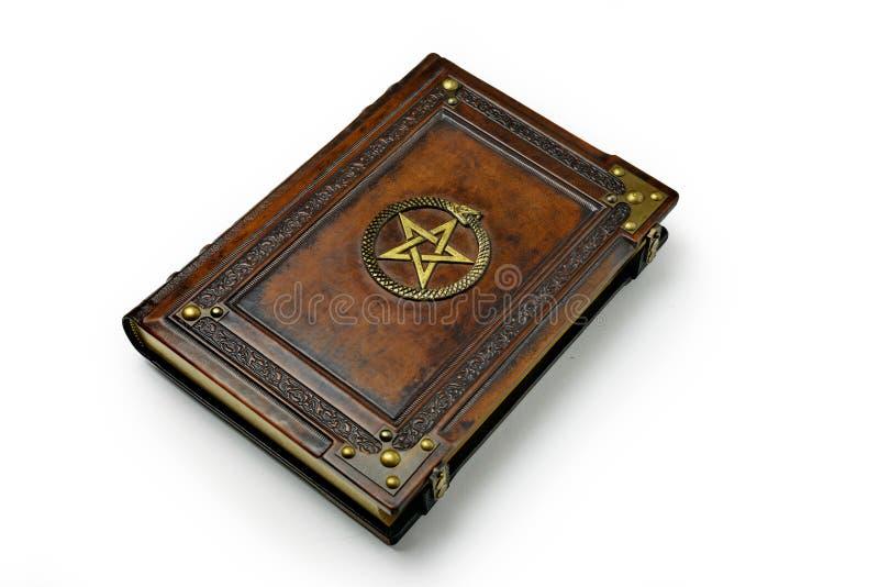 Bryna l?derbokomslag med f?rgylld pentagram och det Ouroboros symbolet som omges med djupt pr?glade ram- och metallh?rn arkivfoto
