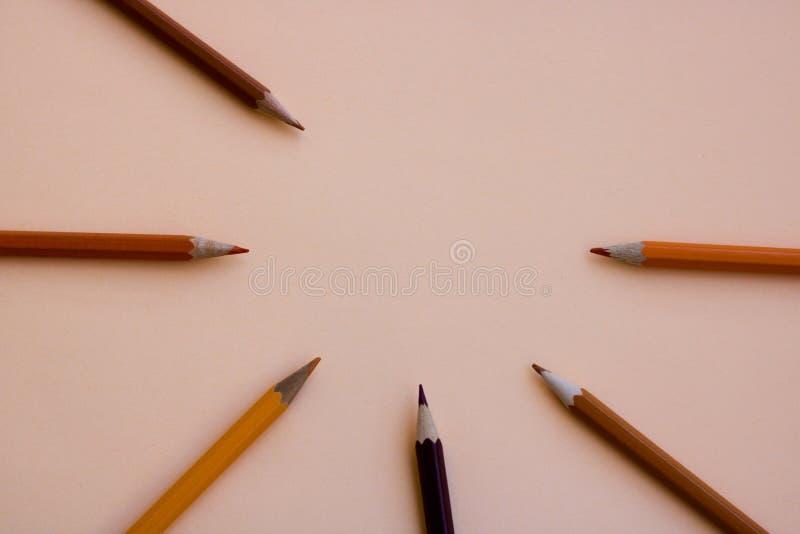 Bryna och gulna färgpennor på en kulör bakgrundsaprikos arkivfoto