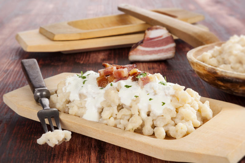 Bryndzove halusky. Potato dumplings with bryndza sheep cheese and bacon on dark woodne background. , traditional national slovak food stock photography