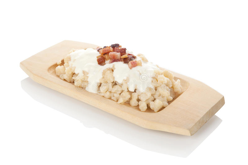 Bryndzove halusky. Potato dumplings with bryndza sheep cheese and bacon on traditional wooden plate. Bryndzove halusky, traditional national slovak food royalty free stock photos