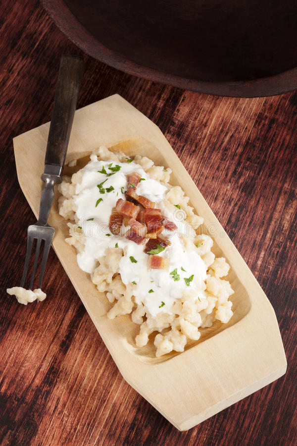 Bryndzove Halusky. Potato dumplings with bryndza sheep cheese and bacon on wooden plate on wooden background, top view. National traditonal slovak food stock image