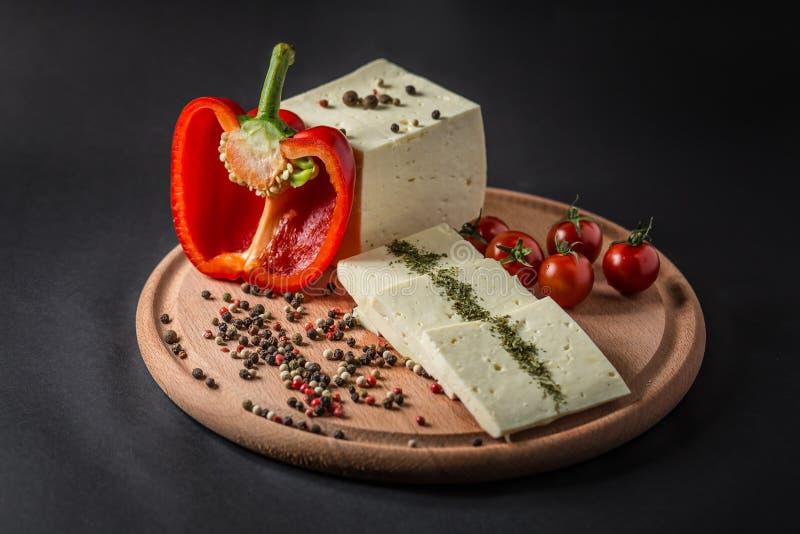 Brynza sul bordo di legno con i pomodori, i peperoncini rossi, le olive, il pepe e le spezie verdi immagine stock