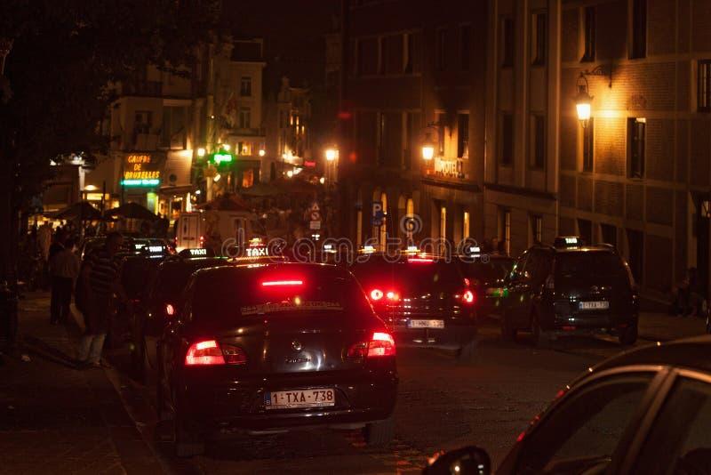 BRYSSEL BELGIEN - SEPTEMBER 06, 2014: Nattsikt av svarta bilar för en taxi som parkeras på vägrenen i den historiska delen royaltyfri foto